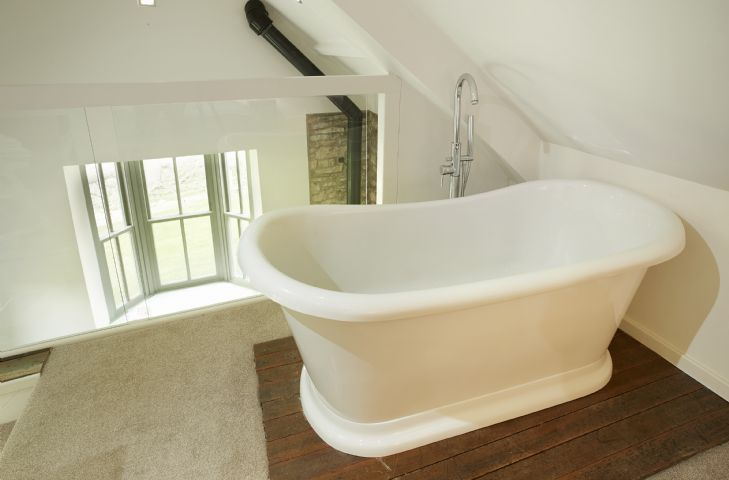 Master bedroom with freestanding roll top bath and handheld shower attachment