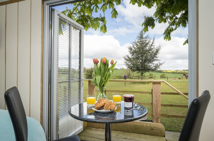 The dining table has glorious views through the french doors on to open countryside