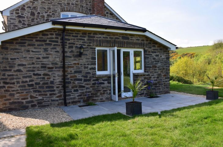 The recent extension providing a dual aspect, ground floor bedroom with sitting area, en-suite shower room and french doors opening onto the garden