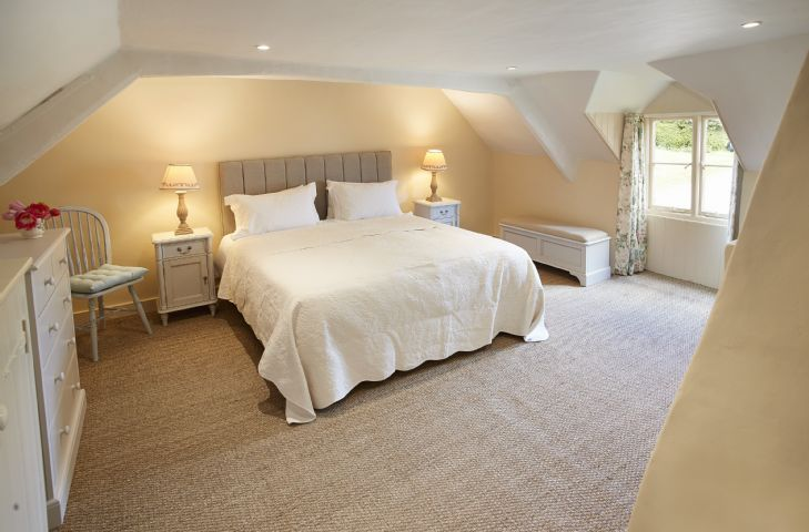 First floor: Large refurbished master bedroom with stylish neutral colour scheme spacious king size bed and built-in wardrobe with sea grass carpets