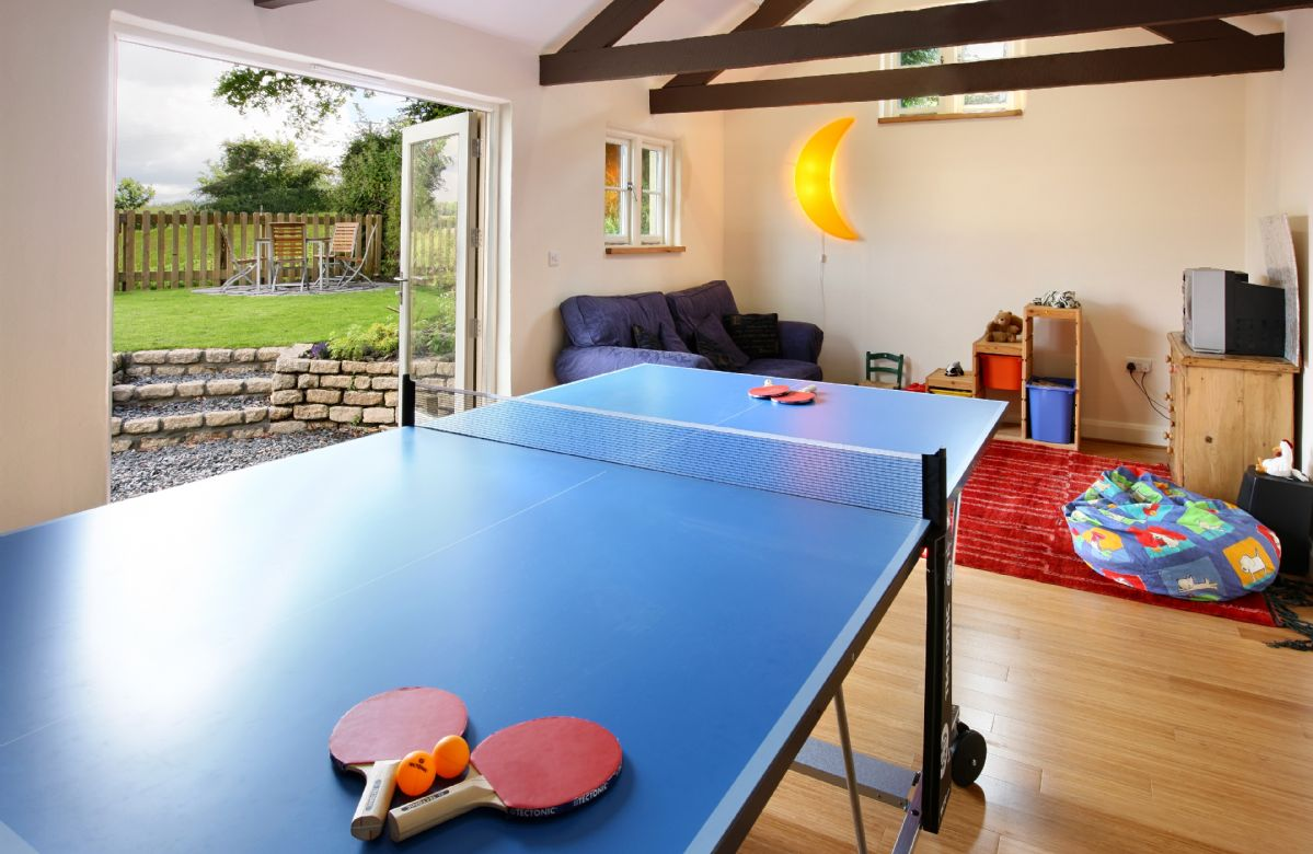 Separate games room with pool and table tennis tables and a wide variety of toys and games