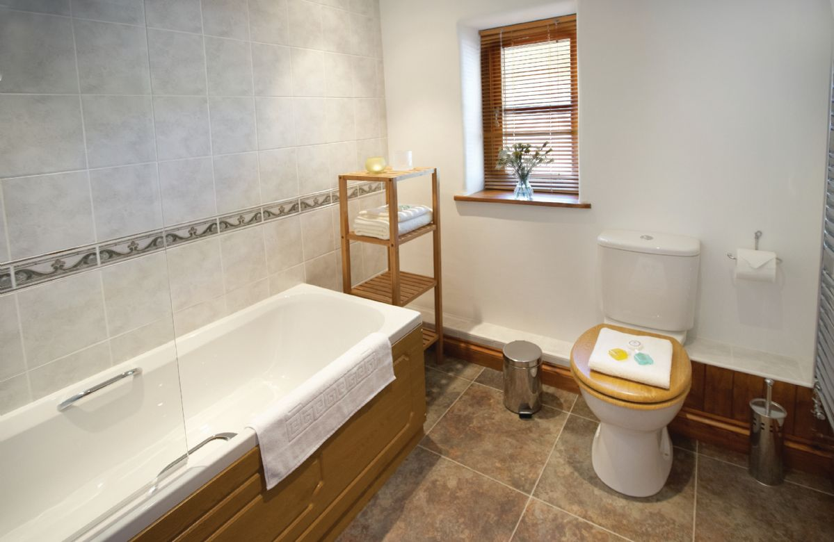 Ground floor: Bathroom with shower over bath, dressing room