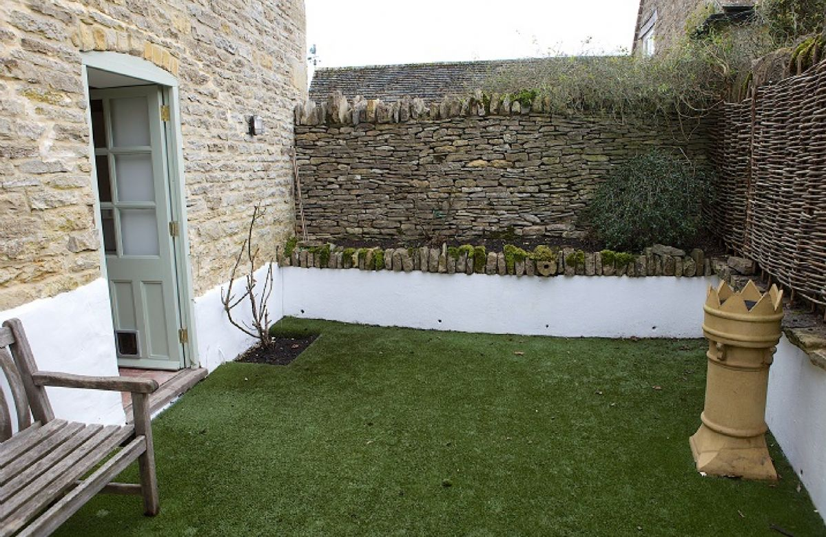 Enclosed rear private garden with raised flower bed and astroturf
