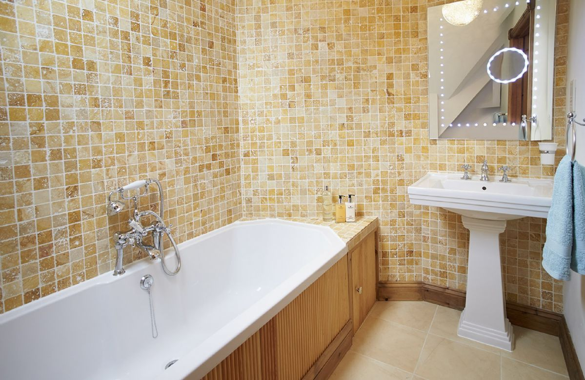 First floor:  Natual stone mosaic tiled en-suite bathroom with Art Deco style suite with large bath and hand-held shower attachment