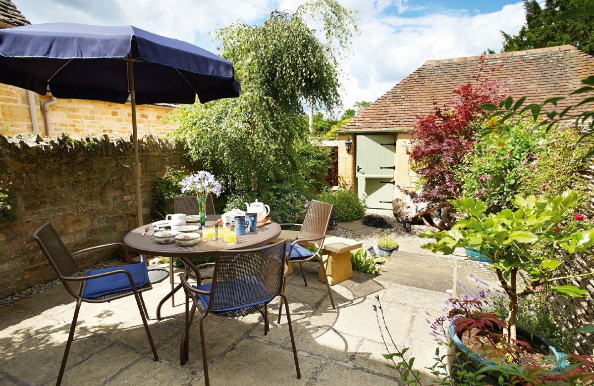 Pretty landscaped garden with garden furniture, and a small stream-like pond with step down to lower level