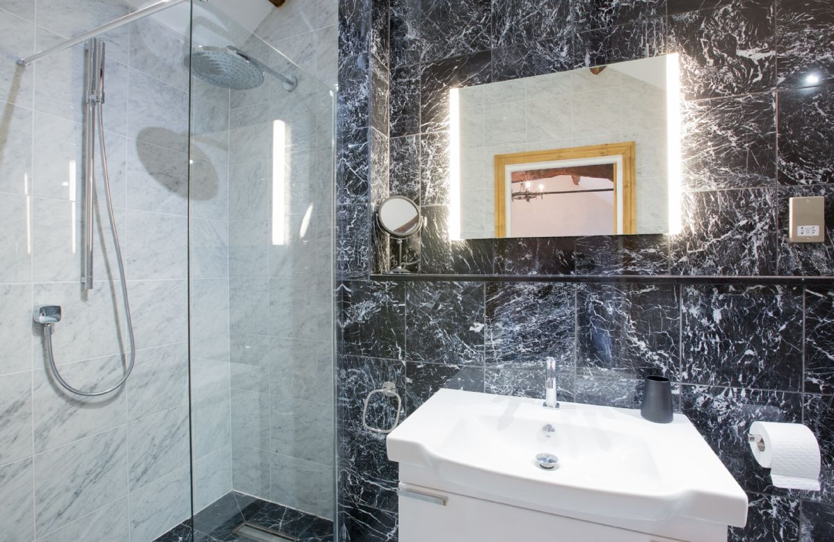 First floor: Martindale - en-suite natural black stone shower room with monsoon and raindrop showers