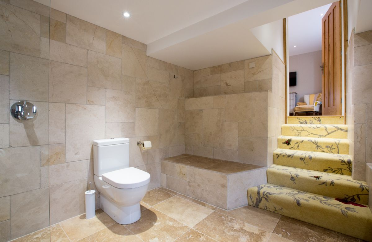 First floor: Bonscale - en-suite subterranean natural stone bathroom with bath and separate monsoon and raindrop showers