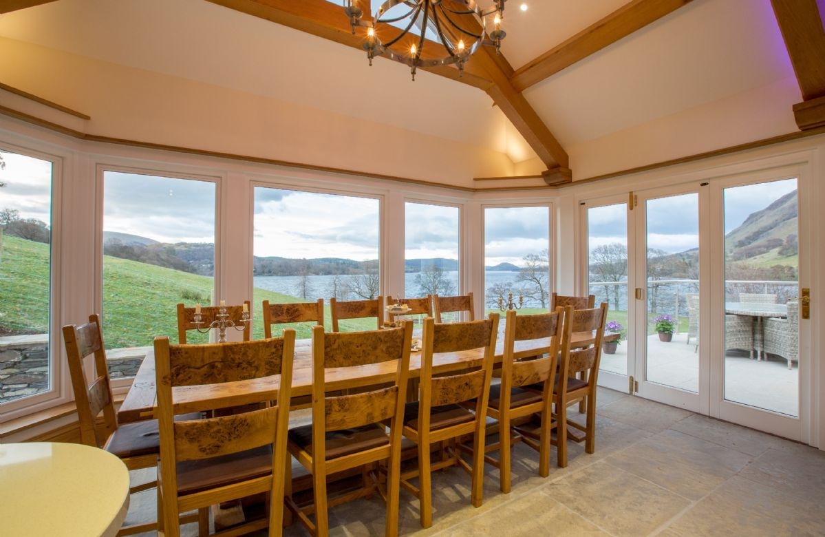 Ground floor: Dining table and chairs seating 12 and double aspect lake views with french doors opening on to terrace