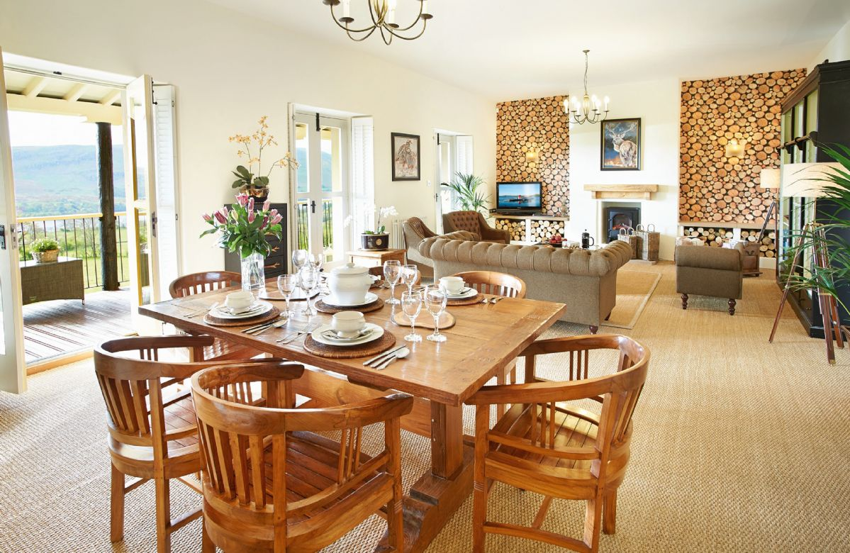 Second floor: Open plan living and dining room with three double doors opening onto a balcony