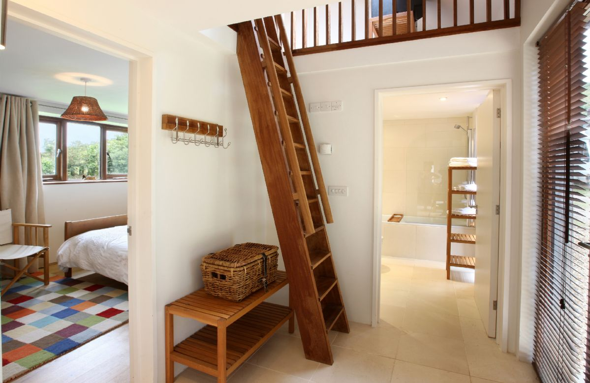 Hall with steep wooden 'ladder' staircase to first floor loft with accommodation for 2 extra older children/teenagers using futon beds. This area leads to gallery bedroom