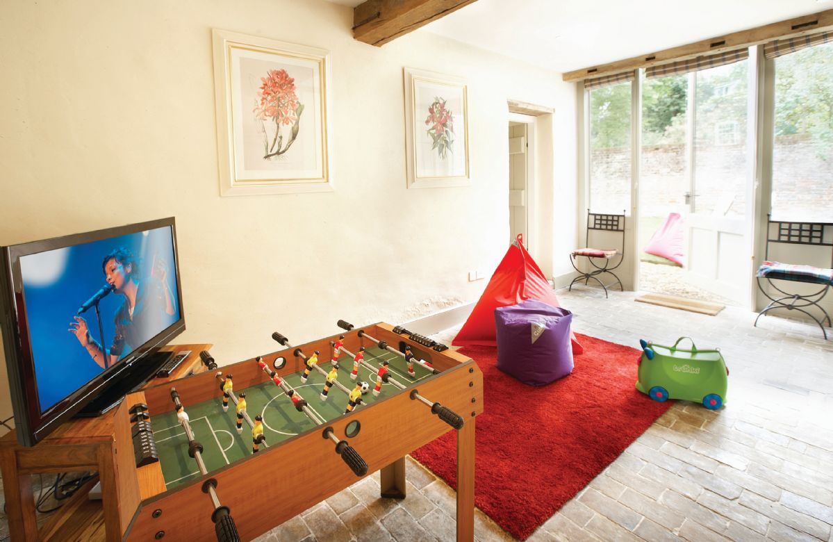 Entertainment room with large screen television, DVD player and French doors leading onto the garden