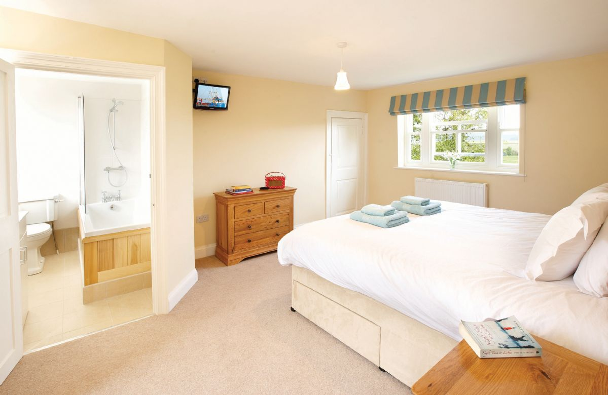 First floor: Double bedroom with a 6' zip and zip bed with en-suite bath and shower over
