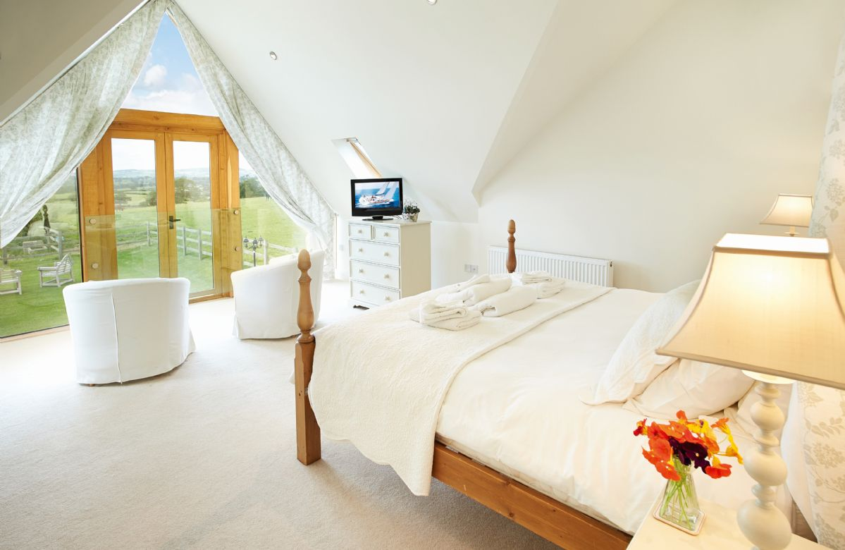 First floor: Master suite with cathedral ceiling and floor to ceiling oak framed glazing providing spectacular views across the beautiful countryside