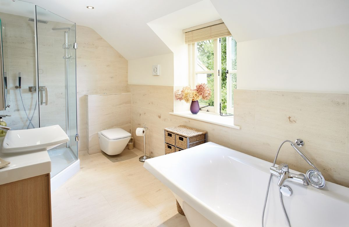 First floor: En-suite bathroom fully tiled with natural stone, designer bath, walk-in shower, luxurious fittings and underfloor heating