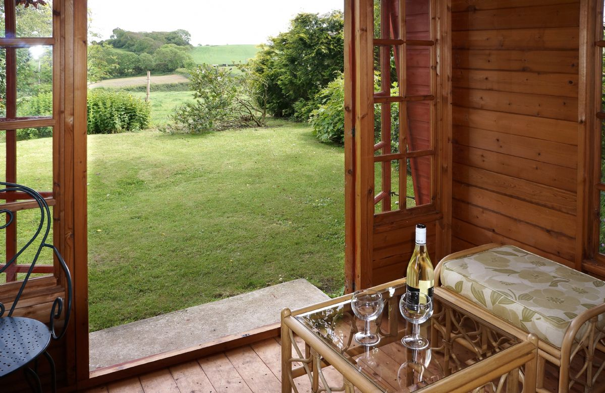 The summer-house looking out onto the gently sloping lawned garden