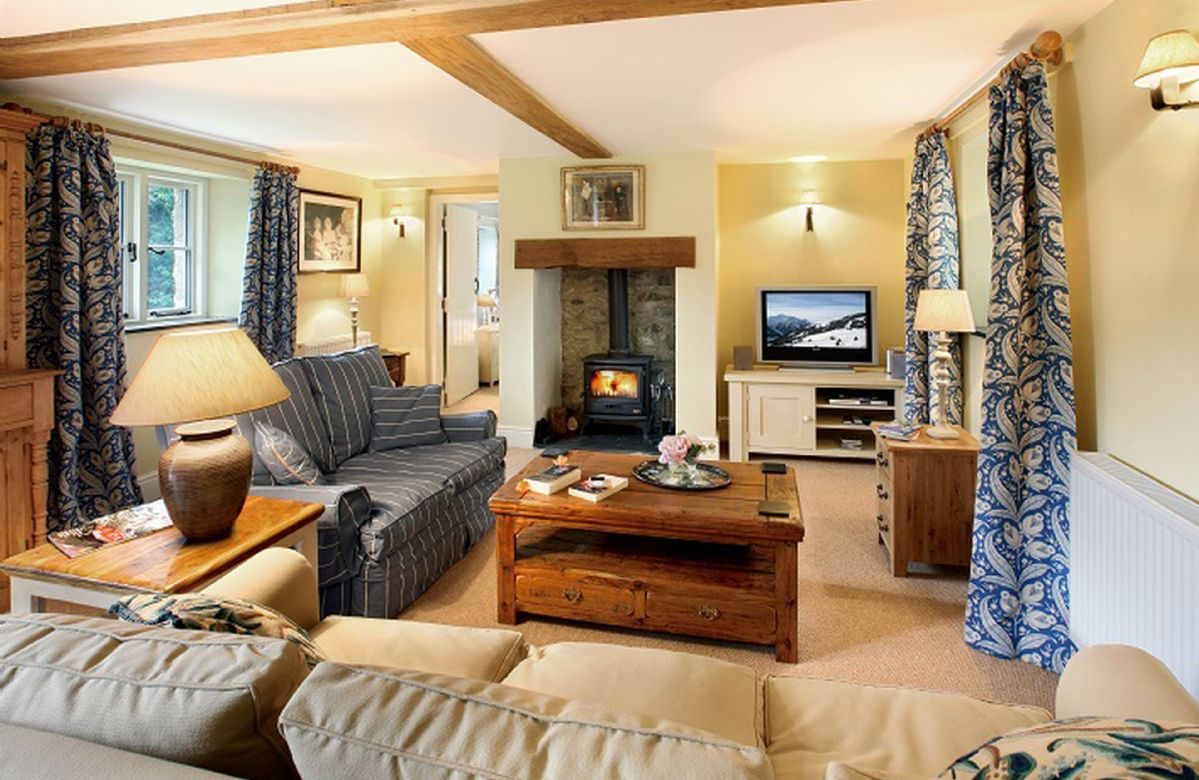 Ground floor:  Sitting room with beamed fireplace and wood burning stove with doors to the garden area