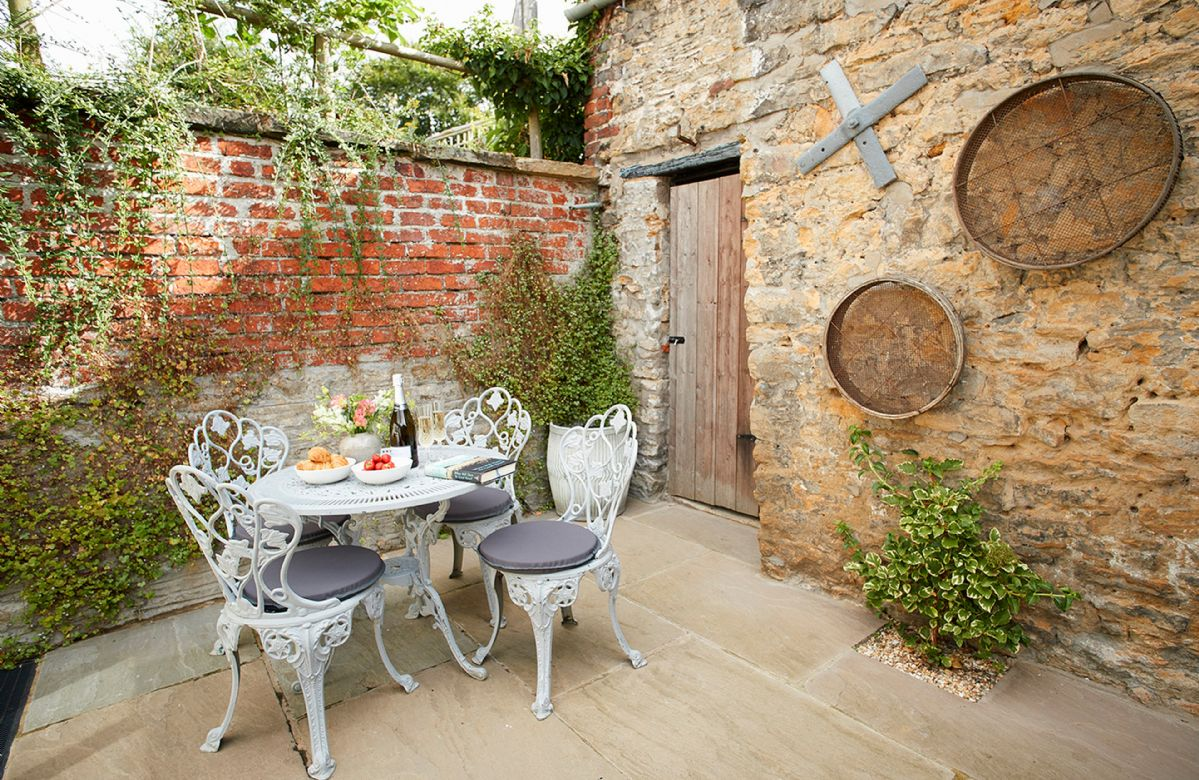 Small pretty enclosed courtyard garden with furniture