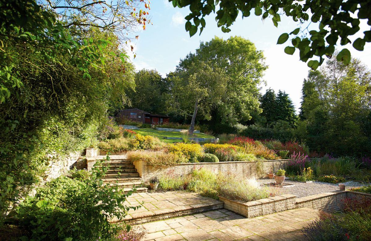 The extensive garden offers views across the valley and both sunny and shaded areas