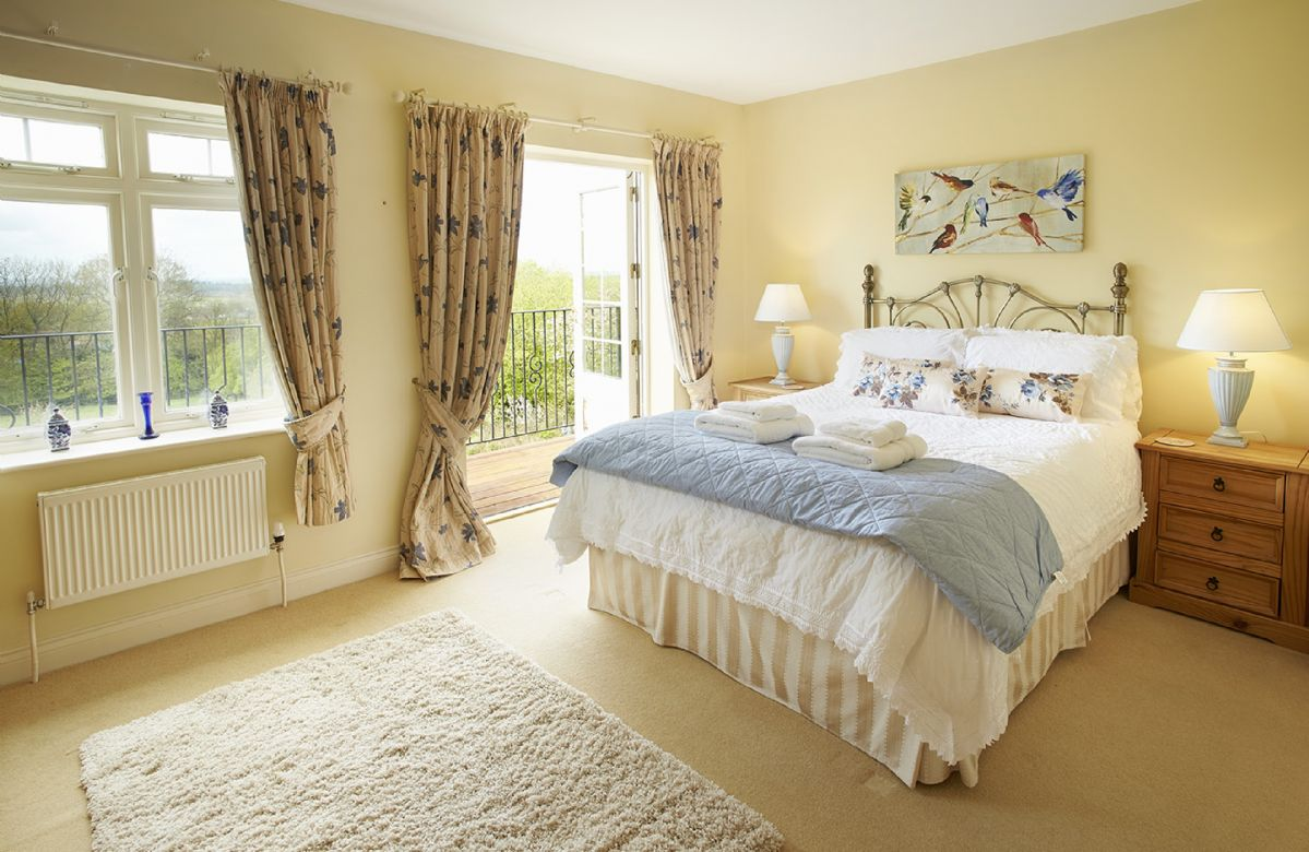 First floor: Double aspect master bedroom suite with separate armchair reading area with a 5' bed and patio doors leading onto the balcony