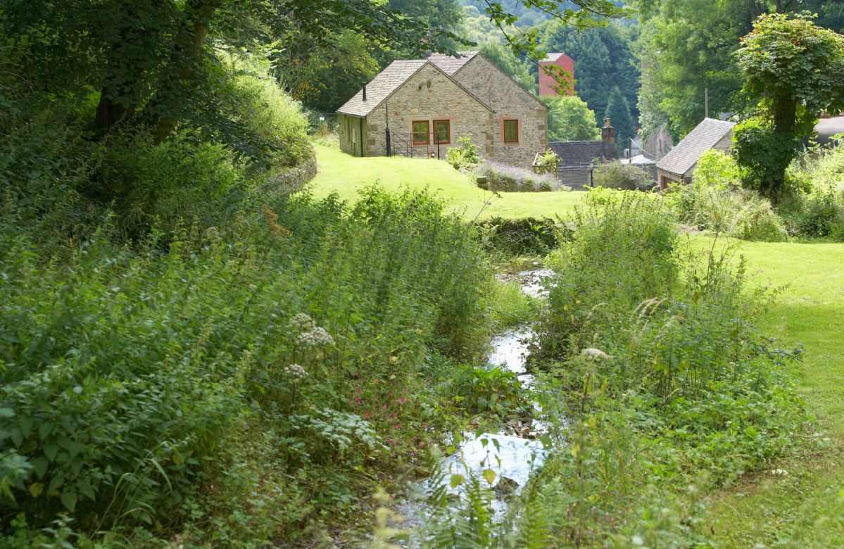 The gardens extend to approximately two acres, the main feature of which is a delightful mill stream which cascades through the gardens over a series of waterfalls, with several small bridges criss crossing the waterway