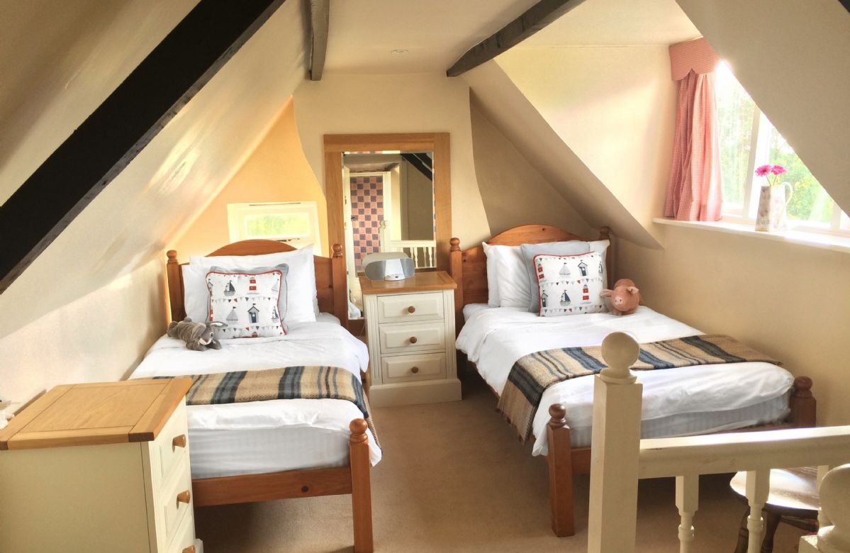 Attic bedroom which has sloping ceilings more suited to children, with twin 3' beds