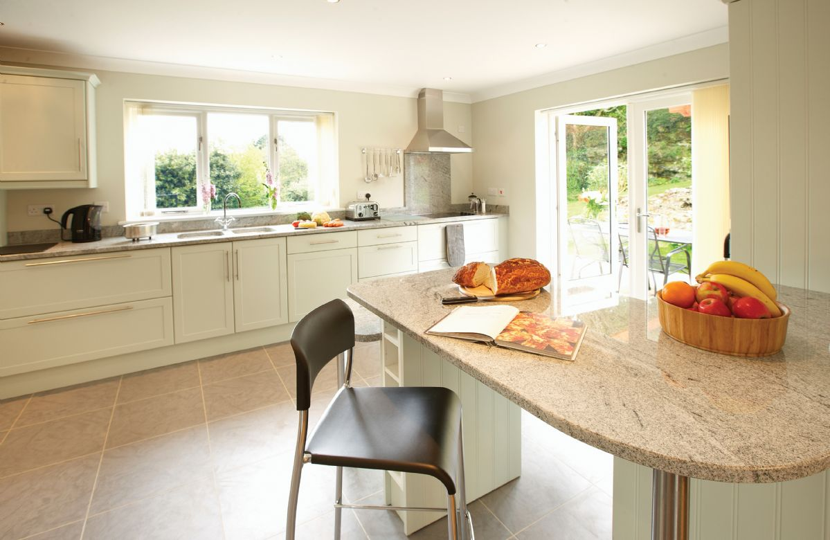 Ground floor: Open-plan kitchen/dining and snug area. The snug has double patio doors onto the rear sun terrace