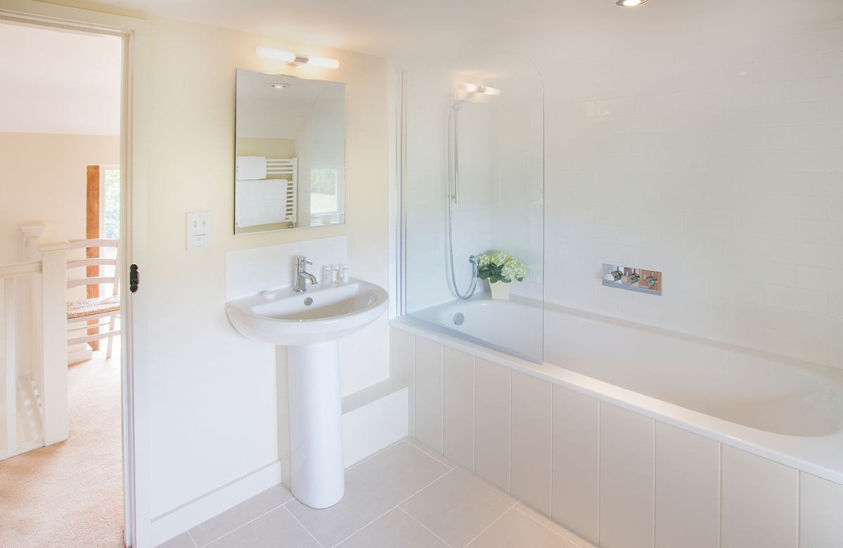 First floor: One of two en-suite bathrooms with power shower