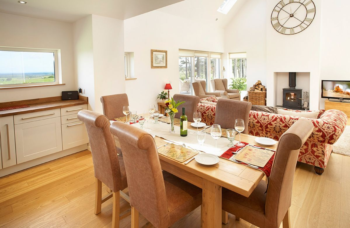 Ground floor:  Dining area and double height sitting room with wood burning stove and stunning views
