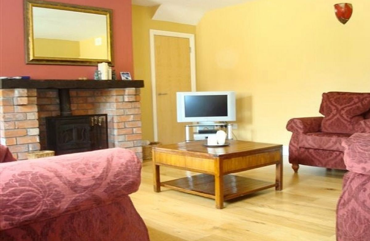Ground floor:  Spacious sitting room with oak floors and multi-fuel stove