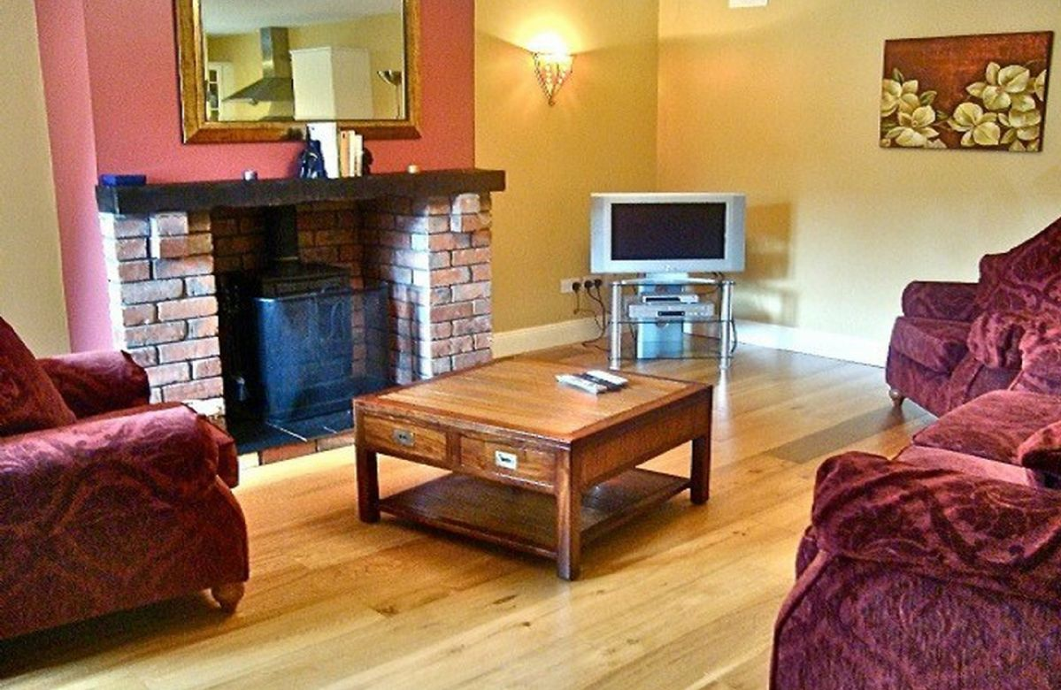 Ground floor:  Sitting room with oak floors and multi-fuel stove