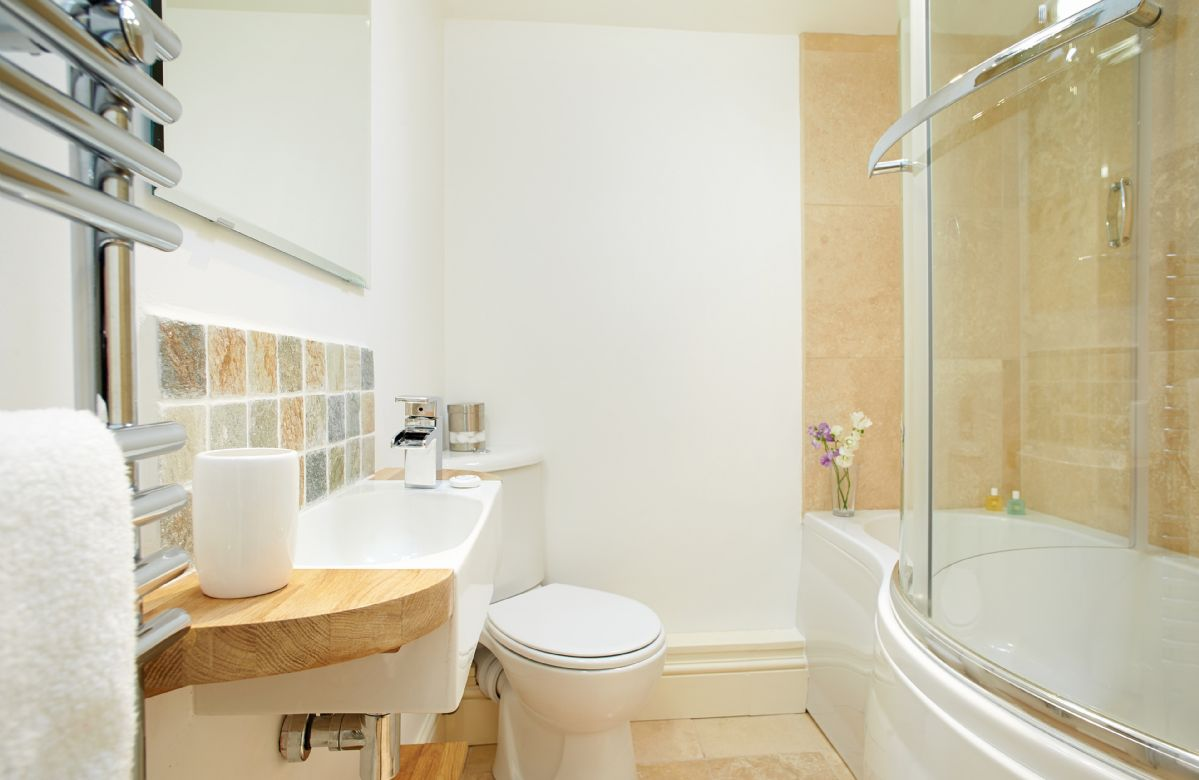 First floor: Bathroom with overheard shower in bath