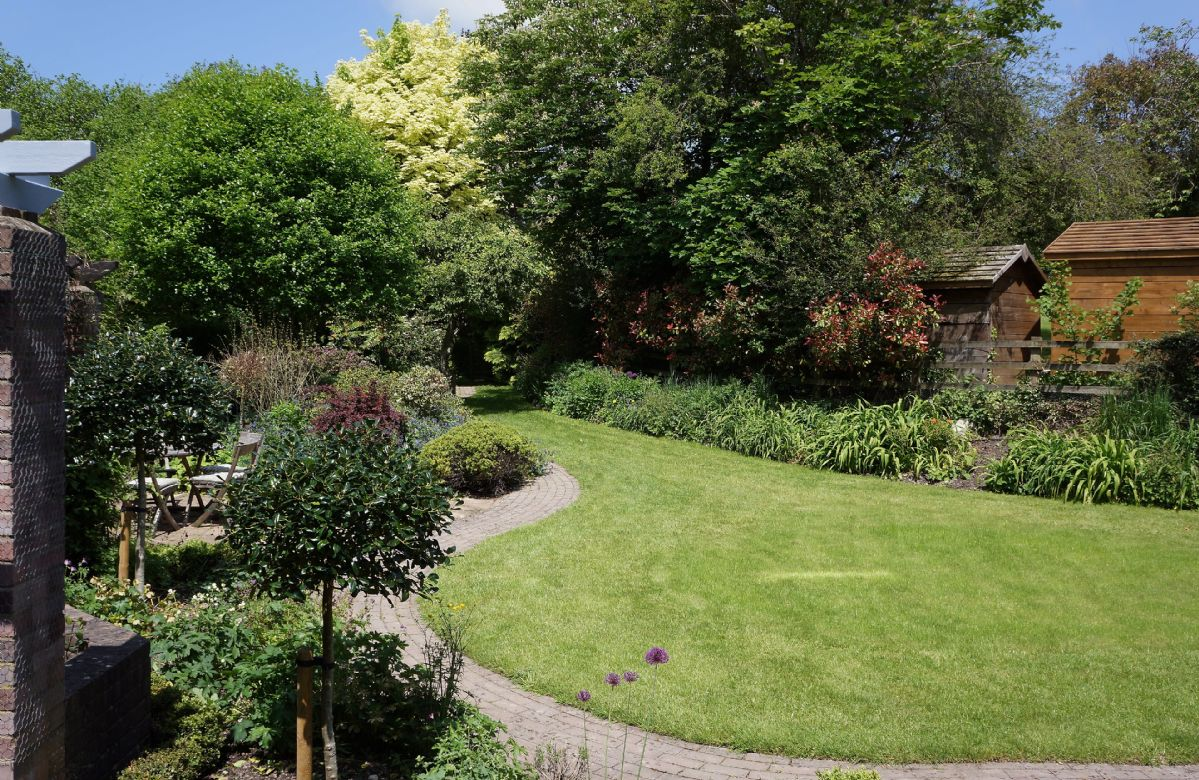 Surrounded by 5 acres of gardens, streams and a wildlife meadow