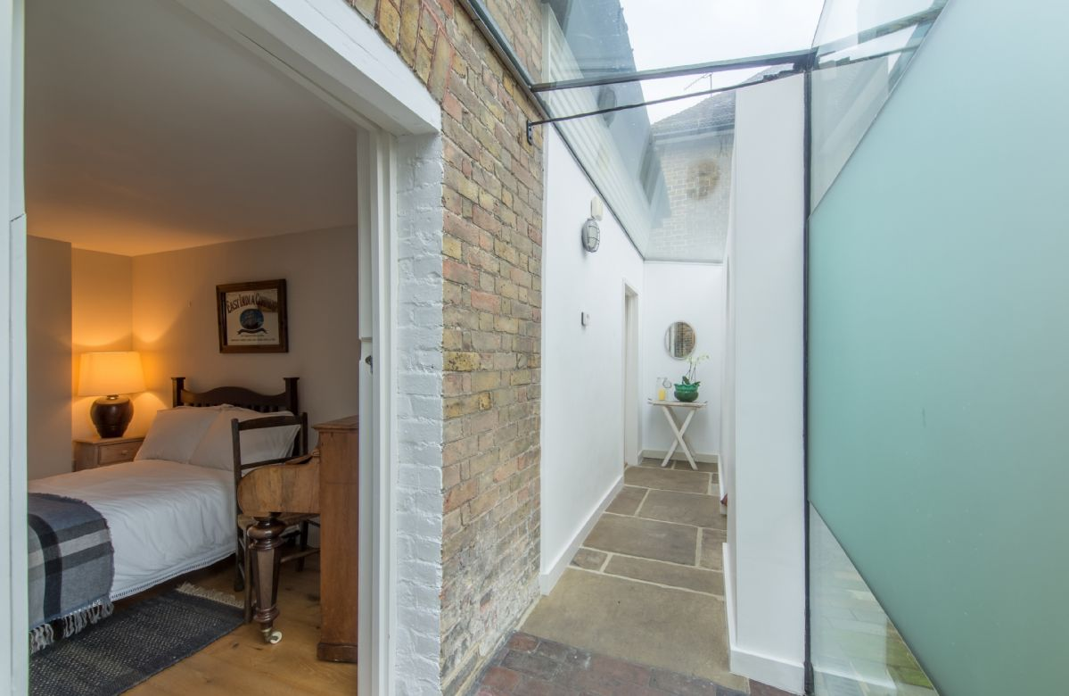 Ground floor: a covered glass walkway leads through to the bedrooms