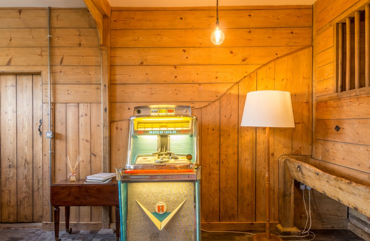 A 1950s jukebox is a fun addition in the entrance hall sitting room