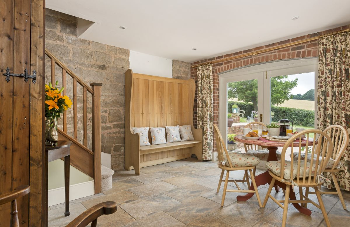Ground floor: Dining area with large glazed doors leading to the terrace and garden