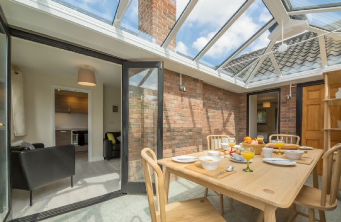 Ground floor: Dining conservatory with doors leading to the garden