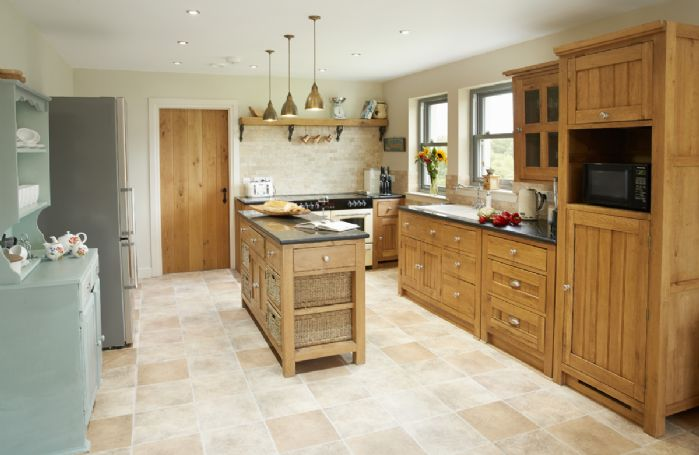 Ground floor: Well-equipped open plan kitchen/family room with range cooker, large comfortable seating area and log burner