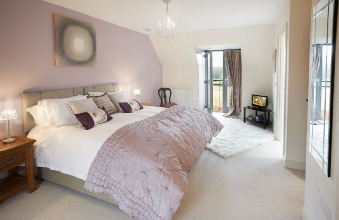 First floor: Double bedroom with a 6' zip and link bed and two Juliette style patio doors with outstanding views