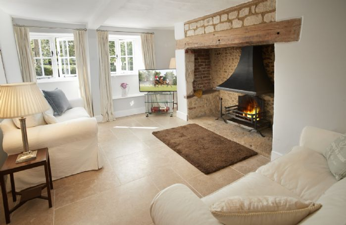 Ground floor: Sitting/dining room with exposed beams and inglenook fireplace with open fire