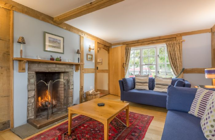 Ground floor: Sitting room with open fire in Cottage