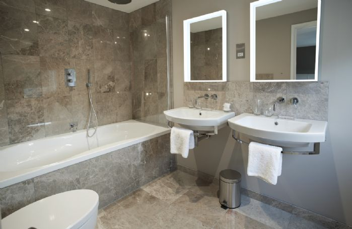 First floor: Bedroom one has an en-suite with double basins, double bath and shower over,