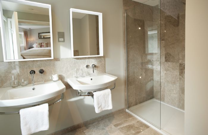 First floor: Bedroom two has an en-suite with double basins and walk in shower