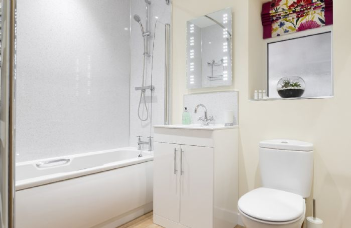 Ground floor: En-suite bathroom with bath and shower over