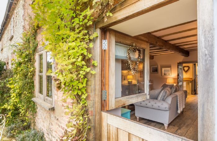 A stable door opens into the spacious sitting room with exposed beams