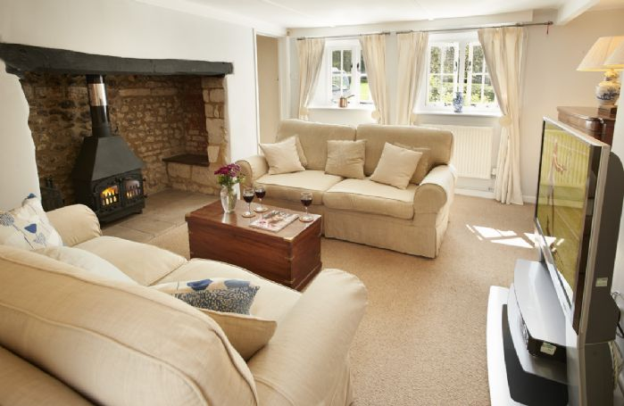 Ground floor: Sitting room with wood burning stove in inglenook fireplace