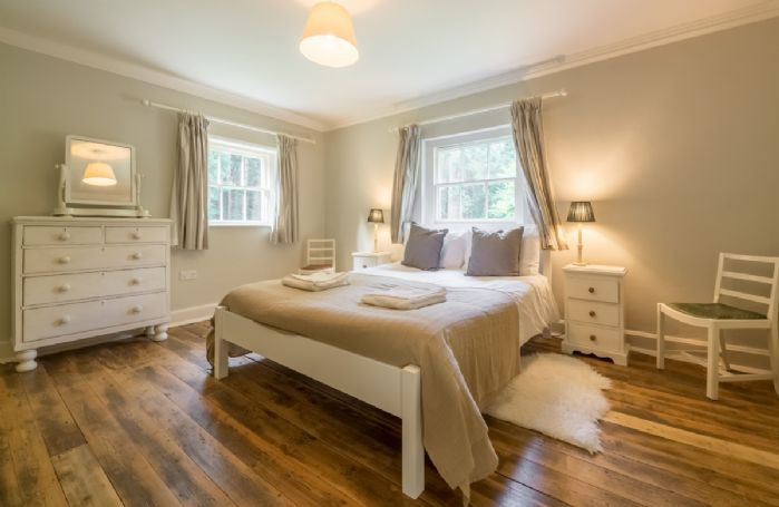 First floor: Bedroom two with 5' king size bed and dual aspect windows with woodland views