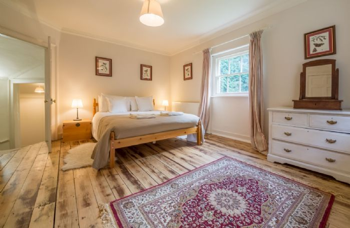 First floor: Bedroom one with 5' king size bed and dual aspect windows with woodland views