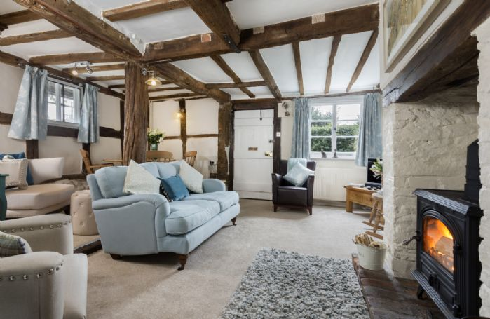 Ground floor: Sitting room with exposed beams, wood burning stove and raised dining area
