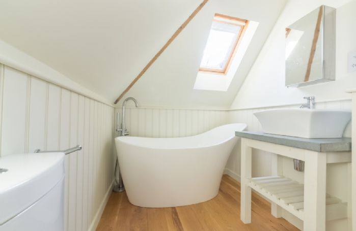 Family bathroom with freestanding slipper bath and handheld shower attachment