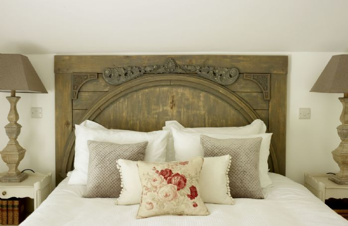 The hand-carved oak headboard completes this romantic space